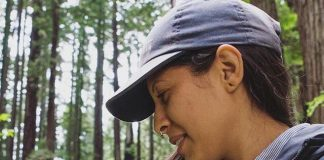 Latina woman in a redwood forest with a banana slug. Photo: Ruby Rodriquez/Latino Outdoors.