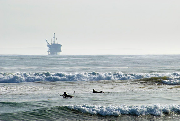 Surfers wait for waves with an offshore drilling platform in the distance in Santa Barbara, CA. Photo: Berardo62, Flickr CC.