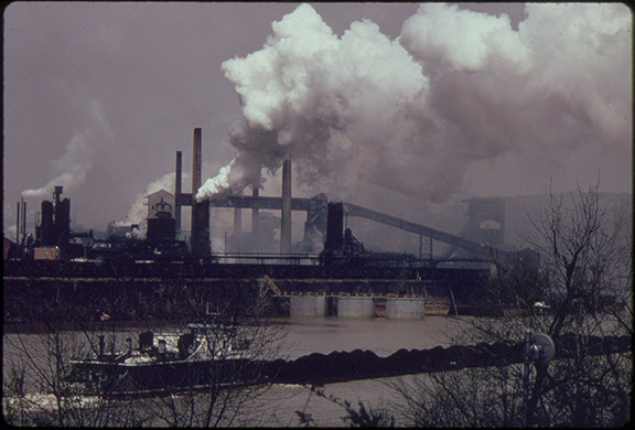 Historic photo of US Steel Corporation coke plant and coal barge at Clairton, PN. The Clairton Coke Works violated its air permit 6,700 times between 2012 and 2015 and was subject to class-action lawsuits due to air pollution as recently as 2017. Plants like these will be under less scrutiny due to Pruitt's rollback of air quality standards.
