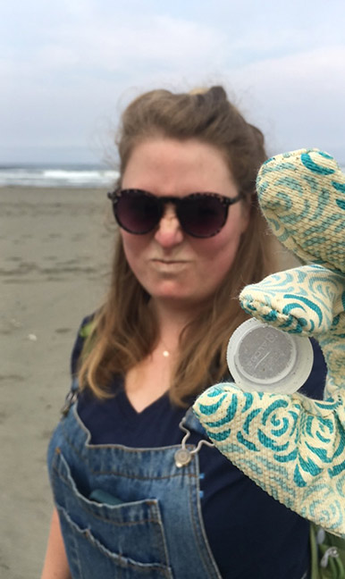 Madison Peters, the NEC's Coastal Programs Coordinator, holds a plastic bottle cap found on a beach.
