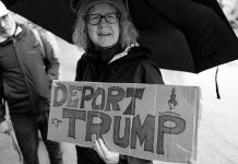 """A protester holds a sign stating """"Deport Trump."""" Photo: vhines200, Flickr.com CC."""
