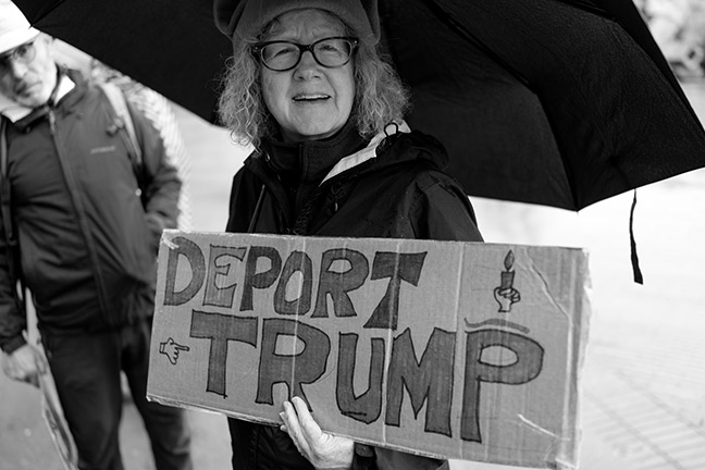 "A protester holds a sign stating ""Deport Trump."" Photo: vhines200, Flickr.com CC."